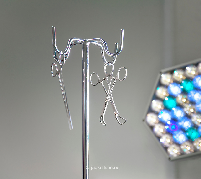 Surgical support equipment. Instrument stand and metal scissors and clamps, lighting rig.