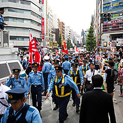 "TOKYO, JAPAN - JULY 16: Japanese nationalists holding Japanese flags (center) took to the streets in a ""hate demonstration"" in Akihabara, Tokyo, Japan on July 16, 2017. The nationalists faced off with anti-racist groups who mounted counter protests demanding an end to hate speech and racism in Japan. (Photo by Richard Atrero de Guzman/NUR Photo)"