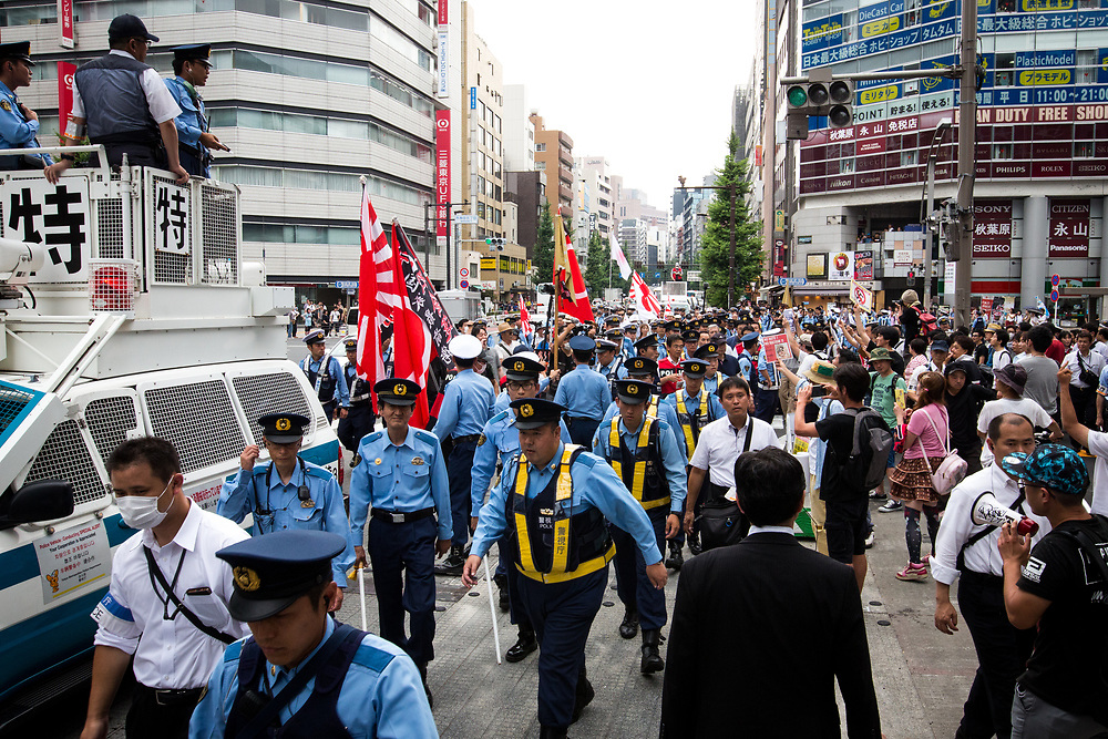 """TOKYO, JAPAN - JULY 16: Japanese nationalists holding Japanese flags (center) took to the streets in a """"hate demonstration"""" in Akihabara, Tokyo, Japan on July 16, 2017. The nationalists faced off with anti-racist groups who mounted counter protests demanding an end to hate speech and racism in Japan. (Photo by Richard Atrero de Guzman/NUR Photo)"""