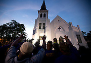 As the congregation of Charleston's Emanuel African Methodist Episcopal Church grieves, a pilgrimage occurs daily at a growing makeshift memorial for nine parishioners killed during a Bible study class. The memorial became a place where anyone could come to heal with prayers, songs, and tears. Just two days after the shootings, the men of Omega Psi Phi Fraternity Inc. raise their hands to lead a crowd in hymns. Each day, hundreds flock to the South's oldest African Methodist Episcopal church to show support and witness the scene.