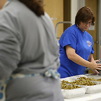 Salvation Army volunteer Amanda Thomason, of Saltillo, pour a can of green beans into a pan as she hepls prepare green bean casseroles for the Salvation Army's community wide Thanksgiving dinner.
