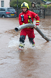 © Licensed to London News Pictures. 13/10/2018. Crickhowell, Powys, Wales, UK. Fireservices pump out The Bridge End Inn, (landlord Howard Baker) at Crickhowell in Powys, Wales, UK.Storm Callum continues to devastate South Wales as the River Usk bursts it's banks as a result of  massive torrential rainfall in Powys flooding many riverside properties. Photo credit: Graham M. Lawrence/LNP