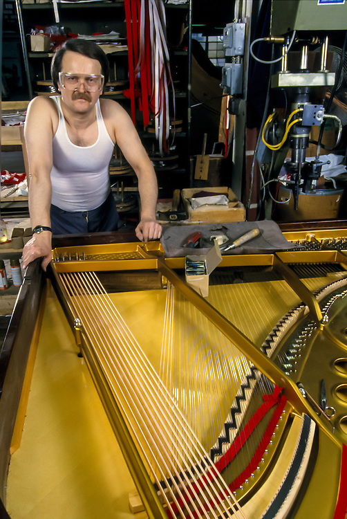 Piano stringer at the Steinway Piano factory, Astoria, Queens, New York.