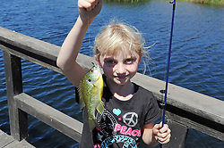 Young Lily Micheli, 7, hold up her eighth catch-and-release of the day at Sunday's Rancho Cielo Family Fun Day in Salinas.