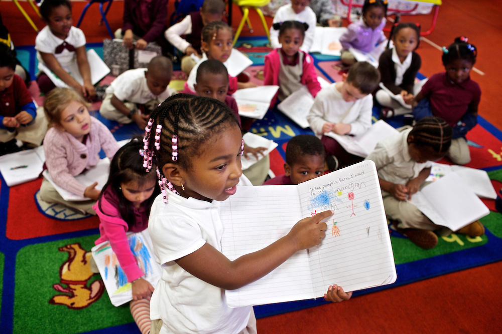 """Calvin Rodwell Elementary School Pre-kindergarten student Morgan Davis, 4, shows teacher Erika Parker and the class what she wrote in her journal after students read the book """"A Day at the Pumpkin Patch,"""" a non-fiction children's book about visiting a farm. The book was part of a """"Common Core"""" reading and learning unit, which aims to follow up non-fiction reading with learning in the field. The day after the children read the book about the farm, they visited Summers Farm in Frederick, MD."""