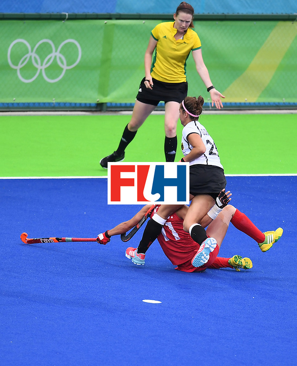 Germany's Pia-Sophie Oldhafer (C) falls over South Korea's Kim Jongeun during the women's field hockey Germany vs South Korea match of the Rio 2016 Olympics Games at the Olympic Hockey Centre in Rio de Janeiro on August, 10 2016. / AFP / MANAN VATSYAYANA        (Photo credit should read MANAN VATSYAYANA/AFP/Getty Images)