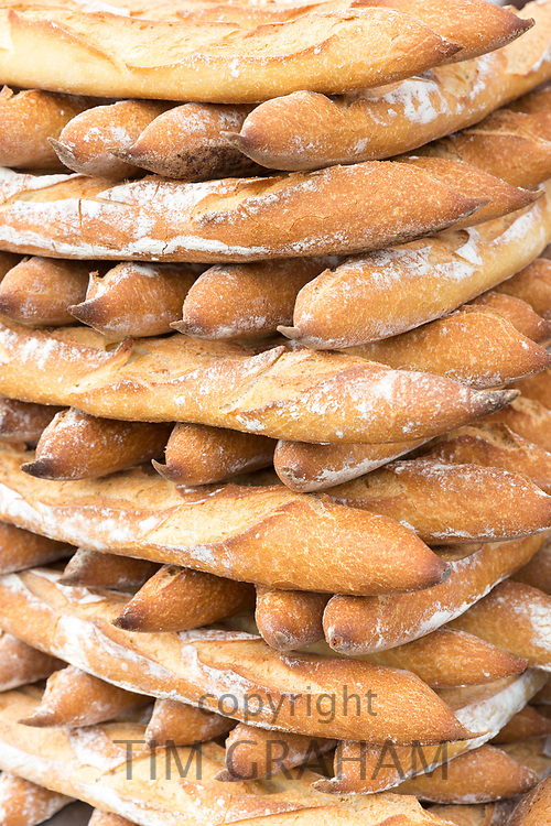 Neatly stacked French fresh baked baguettes on sale at street market in Bordeaux, France