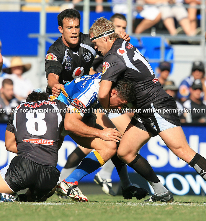 Josh Graham of the Titans is gang tackled by Logan Swan, Michael Luck and Sam Rapira during round 7 of the NRL - Gold Coast Titans v New Zealand Warriors. Played at Skilled Stadium, Robina QLD. Titans (36) defeated the Warriors (24).  Photo: Warren Keir (Photosport NZ).<br /> <br /> Use information: This image is intended for Editorial use only (e.g. news or commentary, print or electronic). Any commercial or promotional use requires additional clearance.