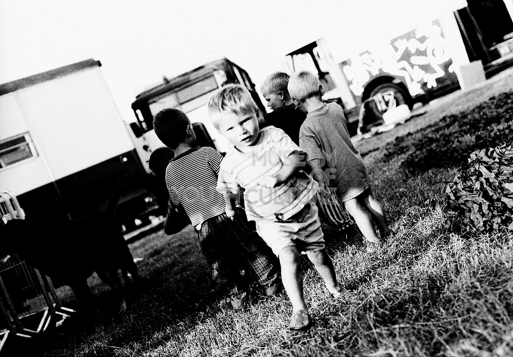 Young kids playing on travellers site, one running towards the camera, 2000's