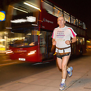 Triathlete Paul Parrish undertakes the run section of his Arch to Arch triathlon attempt through the streets of London September 13, 2014. T