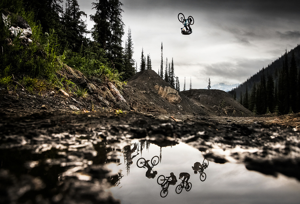"In the remote forests of British Columbia lies Retallack Lodge, a cat-skiing operation in the winter and a mountain bike haven in the summer. I was there to shoot during the making of Brandon Semenuk's ""Rad Company"" movie with himself, Yannick Granieri and Thomas Genon. On the last day of shooting I was able to convince the riders to hit this one particular jump so that I could work a few angles instead of concentrating on a full line of 5 or 6 jumps. It had rained a few days prior to the shoot so some of the mud hadn't dried up yet. I found a clear puddle that I could use to incorporate the reflection of the riders. I set my camera to 1000/sec at f5.0 and ISO 2500 and then rested the bottom of it right on top of the water as I laid in the mud. Both Yannick and Brandon hit the jump several times while Thomas just rolled up the take off, shaking his head and looking worried. I knew he was planning something special, so I just had to be patient and wait for it. When Thomas decided to go for it he didn't give us any warning but from his body language I could tell he was committed to the jump. I shot a sequence and everyone cheered as he rode away. I packed up and that was the end of the shoot."