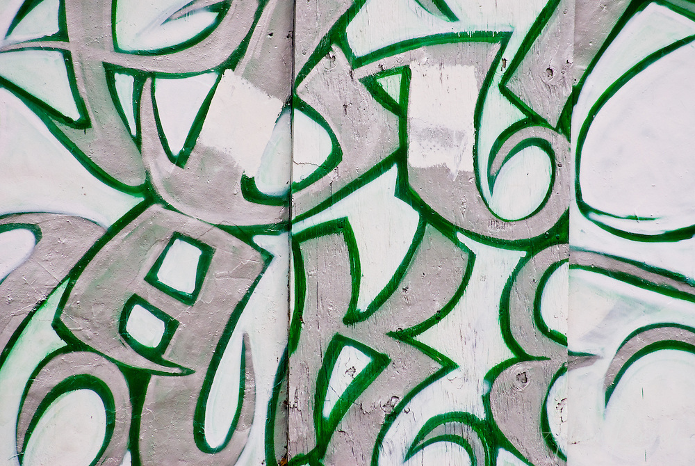 Detail of graffiti, white, green and silver letters across a wall