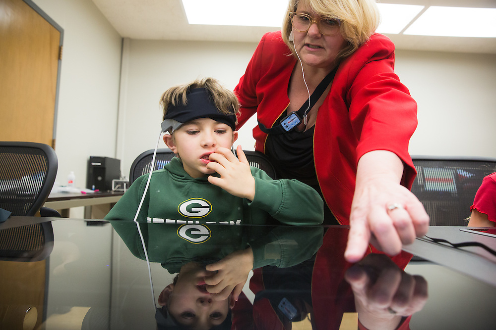 Ramsey Itani, 7, a first-grade student at Sunnyside Elementary in Pullman, Wash., listens to his teacher's, Laura Grant, directions as he wears a Functional Near Infrared Spectroscopy device during a field trip to the Washington State University neurocognition sciene lab Monday, Feb. 22, 2016.