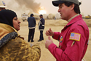 "Brian Krause, president of Boots and Coots, talks with Sara Akbar, development specialist for the Kuwait Oil Company, and member of the firefighting team from the company's (KWWK: Kuwait Wild Well Killers) as they prepare to extinguish the first oil well fire in Iraq's Rumaila Oil field. After dousing the flames with high pressure water hoses, they sealed the spurting well of gas and oil with drilling mud using what is called a ""stinger,"" a tapered pipe on the end of a long steel boom controlled by a bulldozer. Drilling mud, under high pressure, is pumped through the stinger into the well, stopping the flow of oil and gas. The Rumaila oil field is one of Iraq's biggest with five billion barrels in reserve. Many of the wells are 10,000 feet deep and produce huge volumes of oil and gas under tremendous pressure, which makes capping them very difficult and dangerous. Rumaila is also spelled Rumeilah."