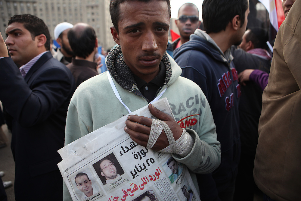 """On """"Sunday of the martyrs"""" at Tahrir Square, an Egyptian man injured in clashes with government forces holds a newspaper with the pictures of those protesters killed over the past weeks of protest."""