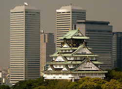 Historic Osaka Castle and contrasting modern financial district buildings in Osaka Japan
