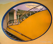 "An interior oval ""window"" gives view to Art Deco staircase, ""padded"" green ceiling and lamp."