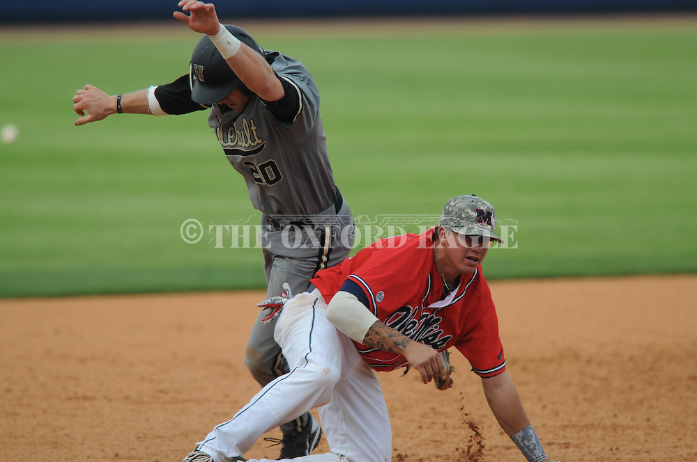 Vanderbilt's Connor Harrell (20) is safe at third and comes around to score the winning run as the ball gets past Ole Miss third baseman Andrew Mistone (25) at Oxford-University Stadium Stadium in Oxford, Miss. on Sunday, April 7, 2013. Vanderbilt won 7-6 in 11 innings.