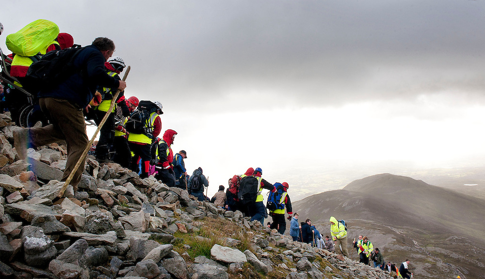 A Mountain rescue teame make their way down  the mountain with a casualty,  Croagh Patrick, Co. Mayo. Pic: Michael Mc Laughlin Thousands of pilgrims navigate up and down the rugged slopes of croagh Patrick in honour of our Patron Saint, Saint Patrick, Ireland's Holy Mountain, Co. Mayo. Pic: Michael Mc Laughlin