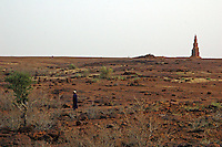 BURKINA FASO, Bani, 2007. Atop the barren landscape a few hundred meters from town, a shepherd surveys the territory near one of Bani's seven mud mosques.