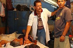 Roberto Hernandez is one of over 1000 Cuban doctors working in Venezuela as part of a government health program.  Hernandez, 38, has spent 2 months of a 2 year stint working in San Pablito, a poor community in Caracas.  Originally from Cien Fuegos, Hernandez has also worked in Angola and the Carribean, spending 2 years in each location.  Here he is giving Antolin Sosa Chacon a check up.  Chacon, bed ridden for 4 days, fell down a hill and had yet to seek medical attention.  Dr. Hernandez believes he suffered a broken wrist and possibly a dislocated knee.  Every afternoon Hernandez makes house calls, and it was during one of these house calls that a neighbor alerted the Doctor to Mr. Chacon's condition.