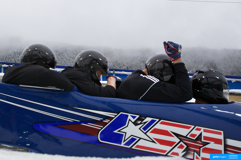 """Winter Olympics, Vancouver, 2010.A USA team load into the bobsleigh during the Bobsleigh Four-man competition  at The Whistler Sliding Centre, Whistler, during the Vancouver Winter Olympics. 25th February 2010. Photo Tim Clayton..'BOB'..Images from the Four-man Bobsleigh Competition. Winter Olympics, Vancouver 2010..History was made at the Whistler Sliding Centre when the USA four-man bobsleigh team, led by Steven Holcomb took the Gold. The first time since 1948, a gap of 62 years, since the USA have won an Olympic Bobsleigh gold and they did it with their sleigh named """"Night Train""""...The four days of practice and competition show the tension, nervousness and preparation as the teams of hardened men cope with the challenge of traveling at average speeds of over 150 km an hour. Indeed, five teams had already pulled out of the event before the opening heats because of track complexity, speed and fear, and on the final day, another four teams did not start after six crashes in the first two heats...Teams warm up behind the start complex, warming muscles in the cold in preparation for the explosive start. Many teams prepare in silence, mentally preparing themselves as they wait at the top of the run, in the bobsleigh sheds and the loading areas for their turn. When it's time to slide each team performs it's own starting ritual, followed by the much practiced start out of the blocks for just over four seconds, the teams are then in the hands of the accomplished drivers as they hurtle down the track for just over fifty seconds...Spectators clamber for the best position on track to see the sleighs for a split second, many unsuccessfully try to capture the moments on camera, The rumble of the sleigh is heard then the crowds gasp as it hurtles past in a blur...The American foursome of  Steven Holcomb, Justin Olsen, Steve Mesler and Curtis Tomasevicz finished with a pooled four-heat time of 3min 24.46sec. The German team led by Andre Lange won the Silver Medal in a combined t"""