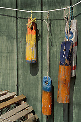 Colorful lobster trap and fisherman buoys on wood shed wall.