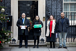 © Licensed to London News Pictures. 12/12/2017. London, UK. Bereaved families from the Grenfell Tower tragedy (L-R: Nicholas Burton, a girl who does not want to be named, Sandra Ruiz and Kareem Mussilhy) hand a petition in at Downing Street, calling for the public inquiry into the disaster to be overhauled. This includes having a panel from a diverse range of backgrounds installed alongside Sir Martin Moore-Bick, the retired Court of Appeal judge leading the process. Photo credit : Tom Nicholson/LNP