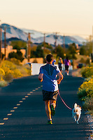 Man running on a path with his dog along Tramway Boulevard, Albuquerque, New Mexico USA