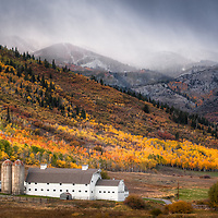 The first snowstorm of the year hits the upper elevations during a strong fall foliage in Park City, Utah. The McPolin Barn was purchased by the citizens of Park City in 1990 to enhance the entrance corridor and maintain open space. Late September 2013