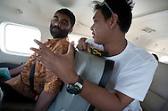 Kumi Naidoo, executive director of Greenpeace International (wearing yellow batik shirt) flies in a plane over Southern Sumatra province to witness first hand the beauty of the forest, and the encroaching destruction of it., in southern Sumatra province, Indonesia, Saturday 16th October 2010. The plantations for paper are owned by Asia Pulp and paper, a subsidiary of Sinar Mas.