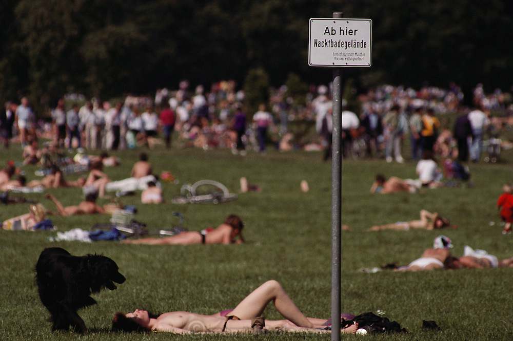 "Sunbathing in the Englischer Garten in Munich, Germany. The sign reads ""Ab hier Nacktbadegelande"" Nude sunbathing area."