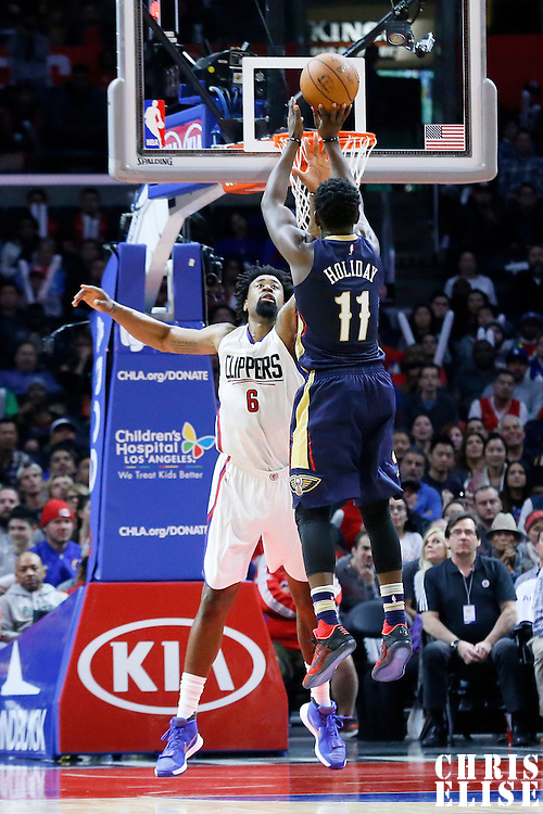 10 January 2016: New Orleans Pelicans guard Jrue Holiday (11) takes a jump shot over Los Angeles Clippers center DeAndre Jordan (6) during the Los Angeles Clippers 114-111 overtime victory over the New Orleans Pelicans, at the Staples Center, Los Angeles, California, USA.