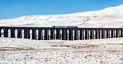 © Licensed to London News Pictures. 27/02/2020. Gearstones UK. A train crosses Ribblehead viaduct in the shadow of the snow covered Wherenside mountain this morning in the Yorkshire Dales after heavy snowfall last night. Photo credit: Andrew McCaren/LNP
