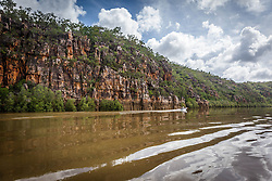 A small dinghy travels past the dramatic cliffs of the Sale River in the Kimberley wet sesaon.