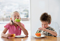 Young girl and boy eating cup cakes at table half length