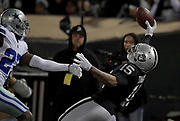 Dec 17, 2017; Oakland, CA, USA; Oakland Raiders wide receiver Michael Crabtree (15) makes a catch as Dallas Cowboys cornerback Jourdan Lewis (27) defends the play during an NFL football game at Oakland-Alameda County Coliseum.