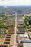 Nederland, Noord-Holland, Amsterdam, 14-06-2012; Burgemeester De Vlugtlaan, levensader van Slotervaart, gezien naar de ringspoorbaan en ring A10. Rechtsonder markt op Plein '40 - '45. Bos en Lommer in het verschiet, binnenstad met IJ en IJsselmeer aan de horizon...De wijk is onderdeel van de Westelijke Tuinsteden, gerealiseerd op basis van het Algemeen Uitbreidingsplan voor Amsterdam (AUP, 1935). Voorbeeld van het Nieuwe Bouwen, open bebouwing in stroken, langwerpige bouwblokken afgewisseld met groenstroken. ..The residential district Slotervaart, one of the western garden cities of Amsterdam-west..  Constructed on the basis of the General Extension Plan for Amsterdam (AUP, 1935). Example of the New Building (het Nieuwe Bouwen), detached in strips, oblong housing blocks alternated with green areas, built in fifties and sixties of the 20th century. Daily market between the flats. The IJ and IJsselmeer on the horizon..luchtfoto (toeslag), aerial photo (additional fee required).foto/photo Siebe Swart