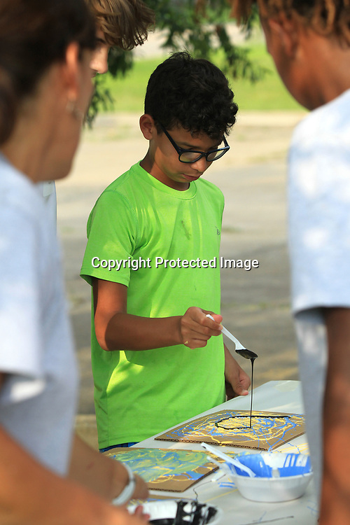 Isaiah Luciano, 12, of Tupelo paints his canvas using the double drip paint method during the Junior Auxiliary WAVE program on Wednesday night at the Tupelo Police Athletic League. WAVE is a weeklong summer camp where boys are encouraged to participate in activites which promote high self-esteem, positive attitudes and healthier bodies and minds. Tupelo Artist William Heard was Wednesday's volunteer at the program and he led the boys in a painting activity.