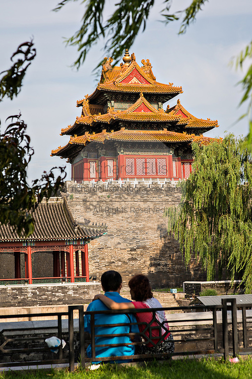 A young couple snuggle by the Arrow Tower on the palace walls of the Forbidden City during a summer day in Beijing, China