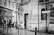 A woman wearing a black coat and hat waits on Rue Rambuteau, on a rainy day in Paris.