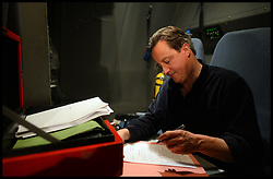 The Prime Minister David Cameron going through papers from his red box on the plane on his way back to RAF Brize Norton  after a visit to see British Troops in Afghanistan. Monday, 16th December 2013. Picture by Andrew Parsons / i-Images