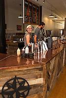 Karen Bassett and Ben Bullerwell working behind the counter at Wayfarer Coffee Roasters on Main Street downtown Laconia.  (Karen Bobotas/for the Laconia Daily Sun)
