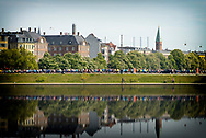 A group of athletes are pictured from afar running by the lakes in Copenhagen with the city as a backdrop.