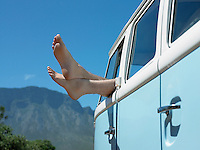 Person in parked camper van feet sticking out of window close up