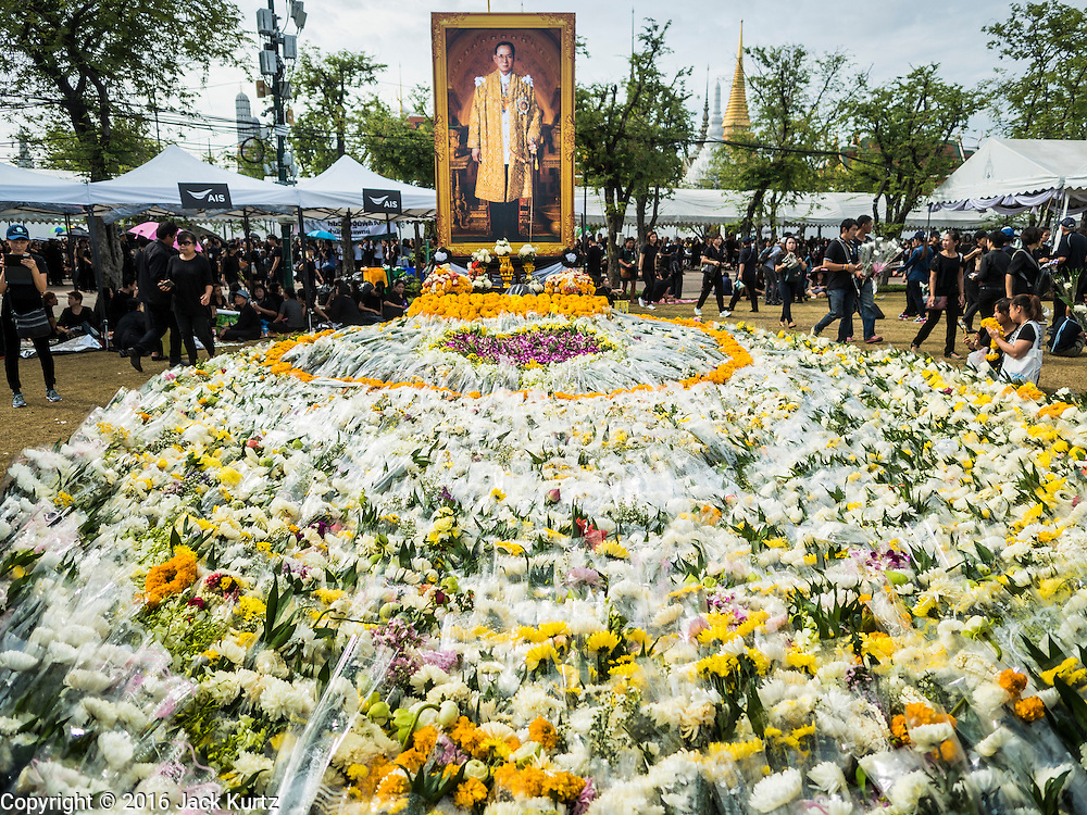 22 OCTOBER 2016 - BANGKOK, THAILAND: A portrait of the late Bhumibol Adulyadej, the King of Thailand, stands over a pile of flowers left by mourners on Sanam Luang. Sanam Luang, the Royal Ceremonial Ground, was packed Saturday with more than 100,000 people mourning the Monarch's death. The King died Oct. 13, 2016. He was 88. His death came after a period of failing health. Bhumibol Adulyadej was born in Cambridge, MA, on 5 December 1927. He was the ninth monarch of Thailand from the Chakri Dynasty and is also known as Rama IX. He became King on June 9, 1946 and served as King of Thailand for 70 years, 126 days. He was, at the time of his death, the world's longest-serving head of state and the longest-reigning monarch in Thai history.       PHOTO BY JACK KURTZ