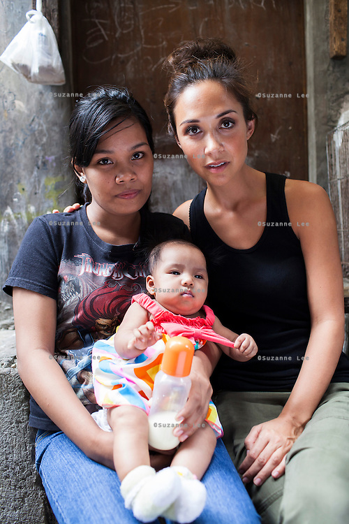 Myleene Klass (right), a celebrity from the UK, meets single mother Josephine Savares, 18, as she holds her 1st child Jihan, aged 4 months, in her neighbourhood, in Paranaque City, Metro Manila, The Philippines on 19 January 2013. After watching advertisements, Josephine had decided to feed her baby formula during her pregnancy and had no idea that her father had to pay such a high price for it. Her family goes without food some days, and her siblings have had to stop school in order to afford the formula. Photo by Suzanne Lee for Save the Children UK