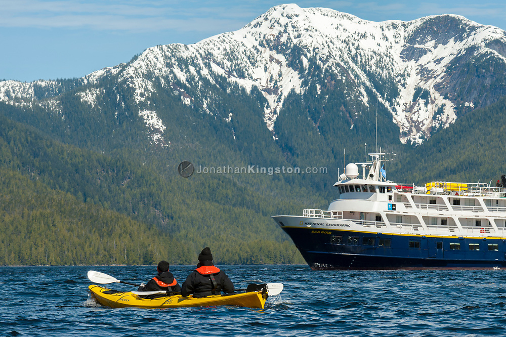 Two people in a yellow kayak with a cruise ship in the background.