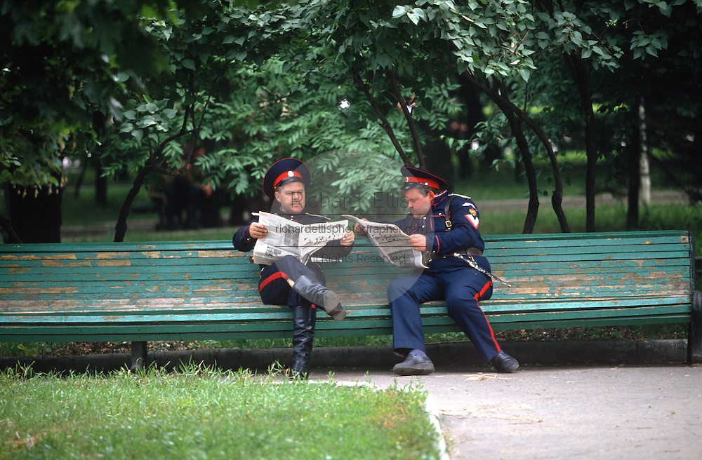 Russian Don Cossacks read a newspaper on a park bench in Novocherkassk, Russia. The men are participating in the annual Cossack Festival gathering of units from around Russia.