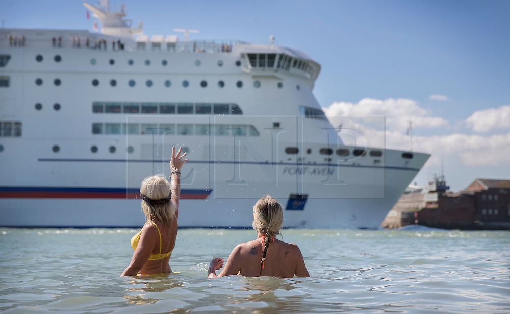 © Licensed to London News Pictures. 30/08/2016. Portsmouth, UK. Swimmers wave at a Brittany Ferry from the beach in Old Portsmouth. High temperatures are being experiences in parts of the United Kingdom today. Photo credit: Peter Macdiarmid/LNP